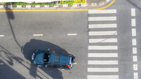 Top view aerial photo of a driving car on asphalt track and pedestrian crosswalk in traffic road with light and shadow silhouette