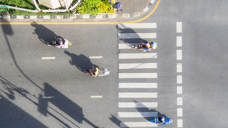 Top view aerial photo of a driving motorcycle on asphalt track and pedestrian crosswalk in traffic road with light and shadow silhouette Stock Photo