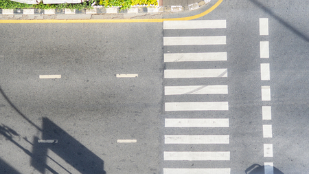 Top view aerial photo of asphalt track and pedestrian crosswalk in traffic road with light and shadow silhouette