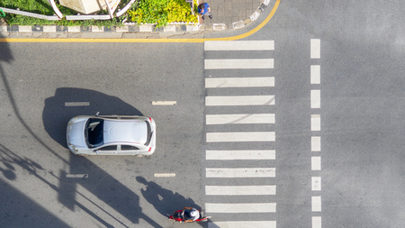 Top view aerial photo of a driving motorcycle and bus on asphalt track and pedestrian crosswalk in traffic road with light and shadow silhouette Stock Photo