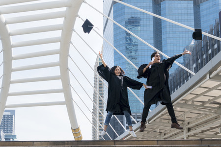 happy graduate teen people jumping with the graduation gowns in congratulation ceremony. Stock Photo