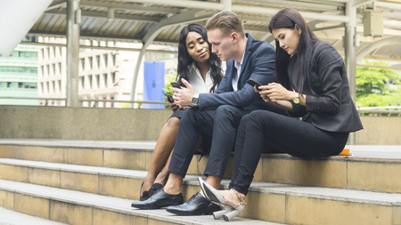 group of three people business use mobile phone and sit on stair and talking