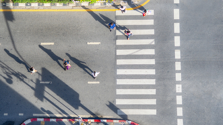 people crowd walk in top view at street city with pedestrian crosswalk in traffic road with light and shadow silhouette