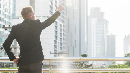 the back portrait silhouette smart business man stands with confident at the outdoor space with the city building background Stock Photo