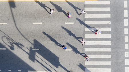 Top aerial view of group people walk at street city with pedestrian crosswalk in transport traffic road with sunlight and shadow silhouette Stock Photo