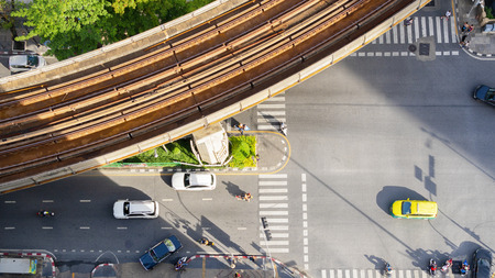 Top view aerial of a driving car on asphalt track and pedestrian crosswalk in traffic road with light and shadow silhouette with rail sky train.