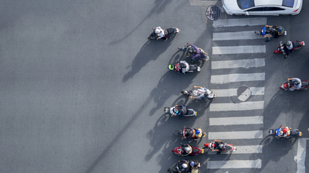 Top view aerial photo of motorcycle driving pass pedestrian crosswalk in traffic road with light and shadow silhouette