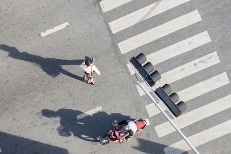 Top aerial view crosswalk with people walk across road with signage. Concept Pedestrians passing a crosswalk. Rush hour in the city Stock Photo