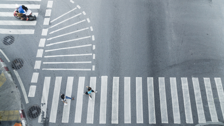 Crowd of people walk on street pedestrian crossroad in the city street with the motorcycle drives pass road ,from top view ,bird eye view. Stock Photo