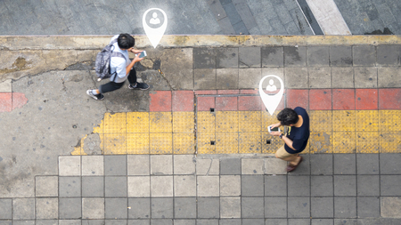 Aerial view and top view with blur man with smartphone is walking in business area with pedestrian street and red and yellow block walkway. concept art of person icon connecting.