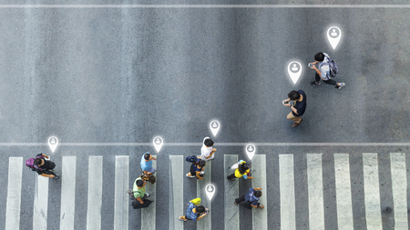Aerial view and top view with blur man with smartphone walking with busy city crowd move to pedestrian crosswalk. concept art of person icon connecting. Stock Photo