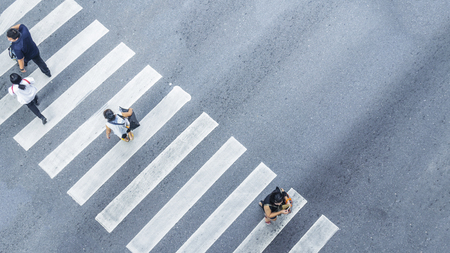 From the top view of people walk on street pedestrian crossroad in the city street with the motorcycle drives pass road ,bird eye view. Stock Photo