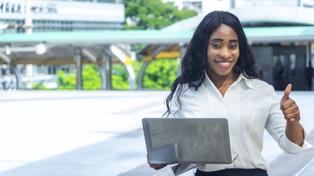 Portrait of happy and confident business african woman uses computer laptop in the outdoor with the city space background
