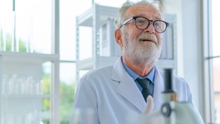 Senior professor male researcher think with face concentration about lab testing science. with interior white lab and equipments on desk. Stock Photo