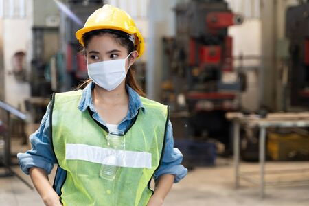 Asian women worker factory wearing mask protection face for safety stands in machine industrial factory. Archivio Fotografico