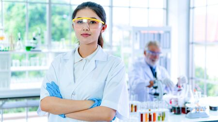 Professor woman researcher white gown stands confident with face concentration. With background interior white lab and the senior scientist prepares testing with equipments on desk.