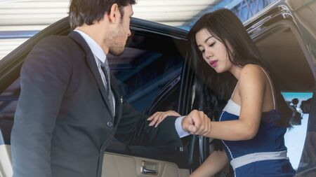 the executive business woman get off from back seat car and smart man holding her hand carefully. Business life executive transport concept. Standard-Bild