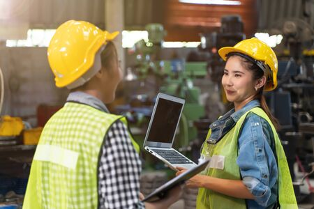 Professional engineering woman worker walk and check in warehouse factory. Manager discuss inspection report paper for internal audit. Quality assurance for manufacturing industry. Concept Engineer Operating with safety.