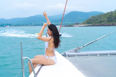 bikini happy girl sit on boat yacht with in front of sea and sky. With jet ski boat drive on background