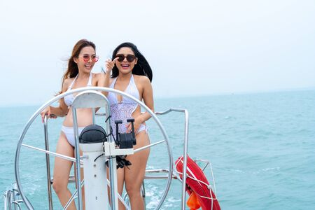 bikini girl stand and dance with driver hand steering wheel on boat yacht with background of sea and sky