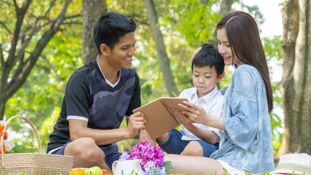 mother and father are teaching kid in park with book.Happy family picnic concept.