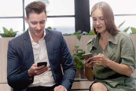 business man and woman using with the mobile phone with someone. Stock Photo