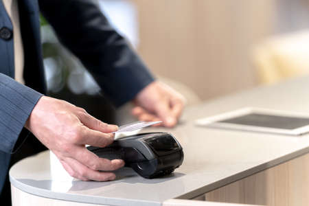 customer hand holding credit card to purchase at counter shop. Concept Contactless payment systems spending money by technology device.