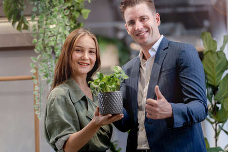 Portrait of happy businessman and woman hold and treat plat pot green trees plant leaves at indoor building garden. Concept office space with biophilia nature.