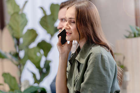 Close up Young Woman Talking to Someone on smart Mobile Phone While Looking Into the Distance with Happy Face. Stock Photo