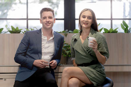 Portrait of happy businessman and woman hold cup of coffee at coffee cafe counter bat with nature biophilia for wellness life. Stock Photo