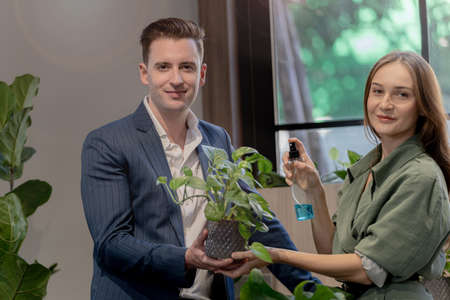 Portrait of happy businessman and woman check and treat green trees plant leaves at indoor building garden. Concept office space with biophilia nature. Stock Photo