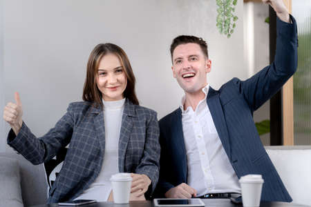 business man and woman hand up and laughing in feeling happy. Successful company achieving goals with determined staff