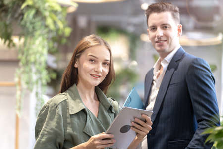Portrait of happy woman holding tablet device and sitting at coffee cafe counter bar with people colleague at background. Concept business coffee time with smart technology working.