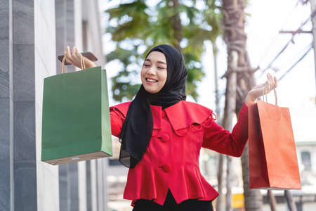 happy face muslim woman in red dress holding shopping bag and walking outdoor street. Concept people activity in shopping festival season christmas and new year. Stock Photo