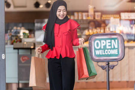 happy face muslim woman in red dress holding shopping bag and walking out shop with welcome open sign. Concept people activity in shopping festival season christmas and new year. Stock Photo