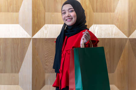 happy face muslim woman in red dress holding shopping bag. Concept people activity in shopping festival season christmas and new year.