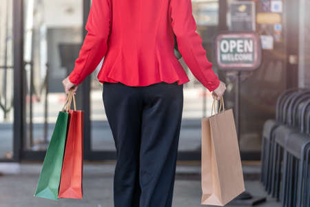 woman in red dress holding shopping bag and walking to shop building. Concept people activity in shopping festival season christmas and new year.