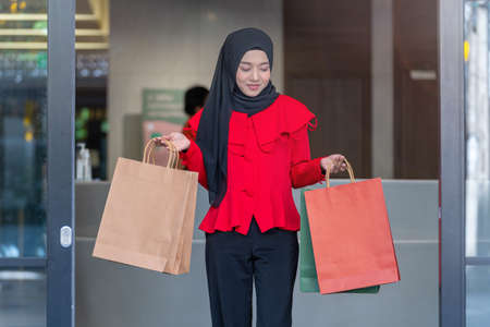 happy face muslim woman in red dress holding shopping bag and walking out shop building. Concept people activity in shopping festival season christmas and new year.