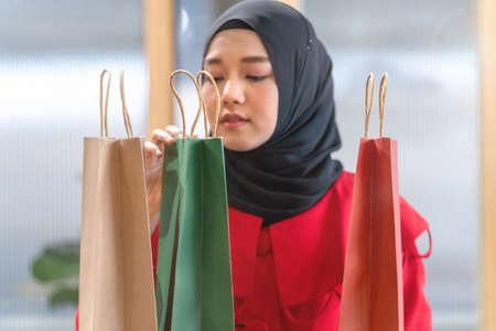 happy face muslim woman in red dress checking shopping bags. Concept people activity in shopping festival season christmas and new year.