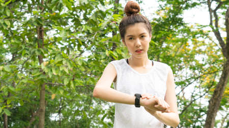 Asian cute healthy fit and firm slim teen lady look at the smartwatch to set GPS or heart rate before running and workout at outdoor garden park