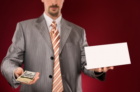 Businessman giving money, blank card in other hand photo