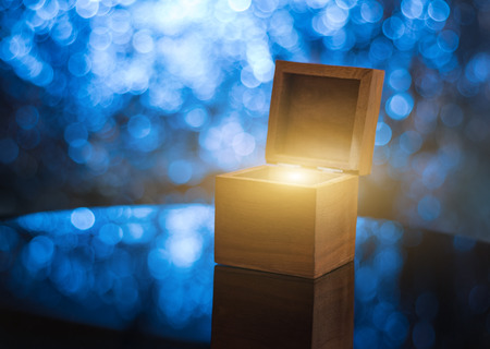 Open wooden gift box with magical light inside, illuminated blue bokeh background