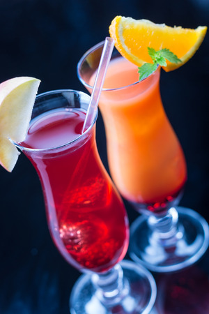 angled view: Two colorful cocktails, garnished with fruit, angled view Stock Photo