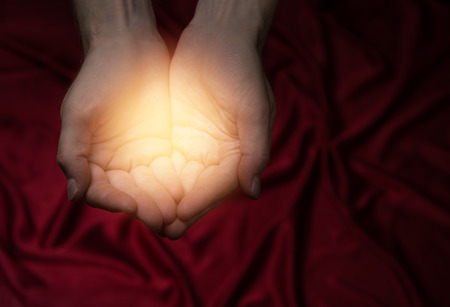 Man holding light in his hands and sharing it, dark red background