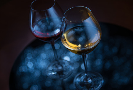 glases: Two glases with wine, silver defocused lights reflection on dark background Stock Photo