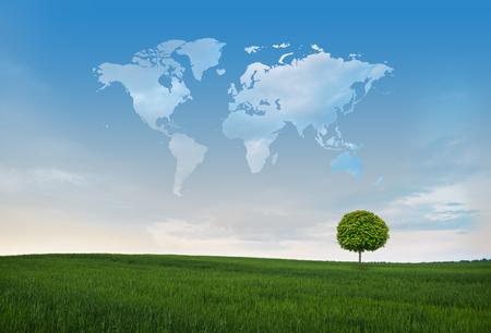 Groen gebied met eenzame boom en wolken in de vorm van de wereldkaart