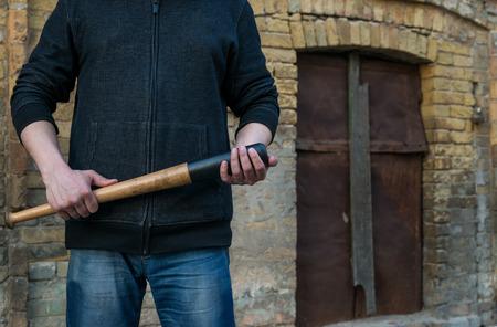 a cudgel: Unrecognizable criminal with cudgel in street