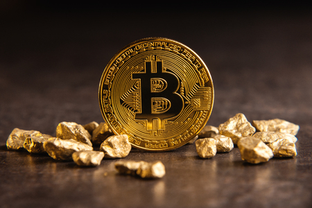 Golden bitcoin and gold nuggets