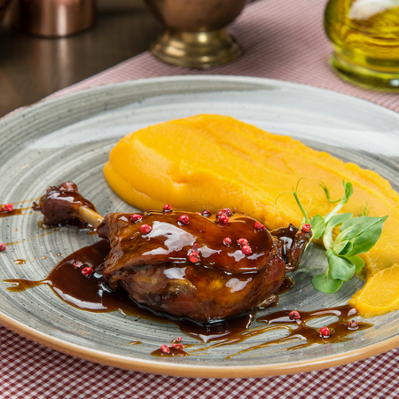 Garnished roasted duck leg with pumkin puree Imagens