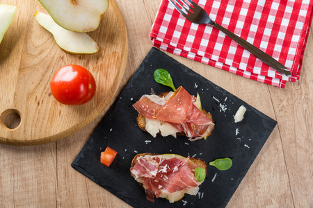 Bruschetta with prosciutto, cheese and pear